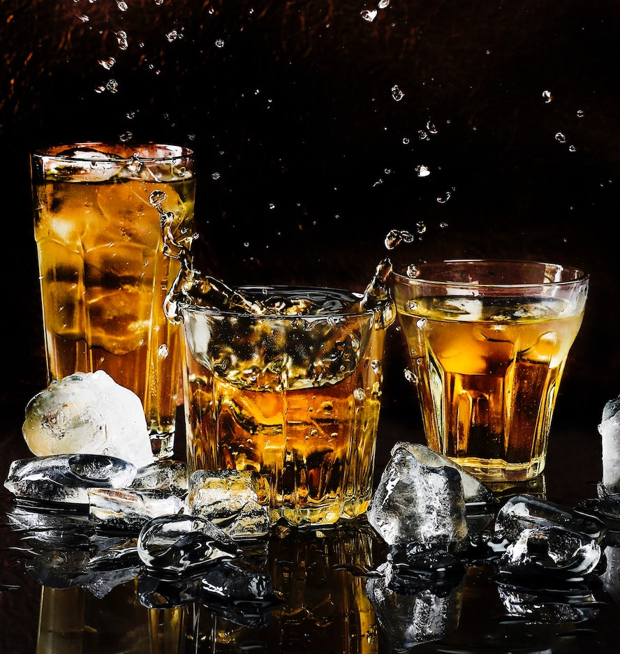 Tumblers of brown liquor over ice
