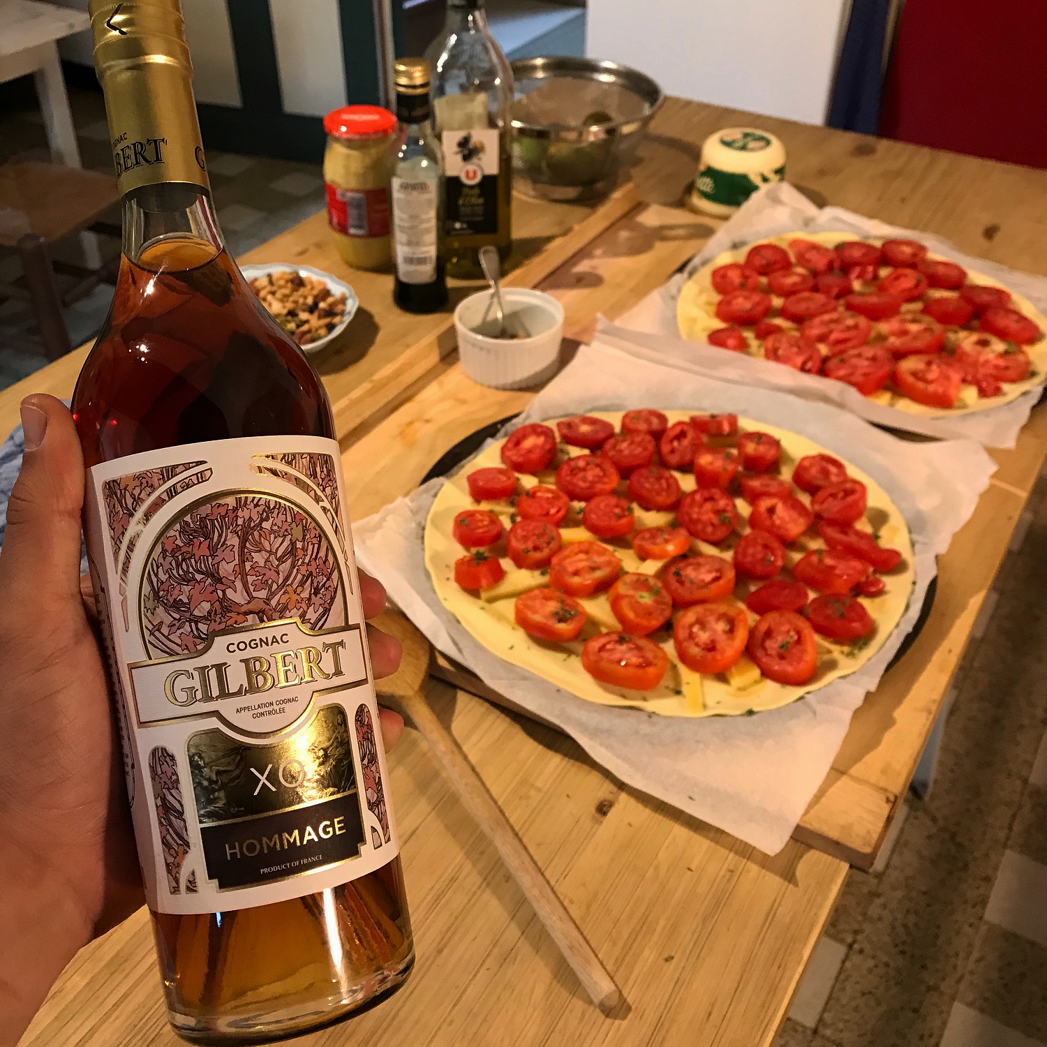 A bottle of Gilbert XO with Pizzas in the background